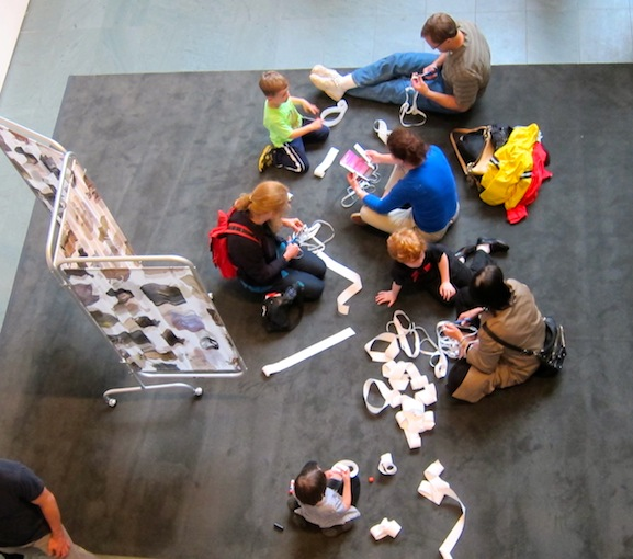 Visitors trying Lygia Clark's proposition, Caminhando on the rug at MoMA Studio: Breathe with Me with Allison Smith's Joining Screens project as a backdrop. Photo by Sarah Kennedy
