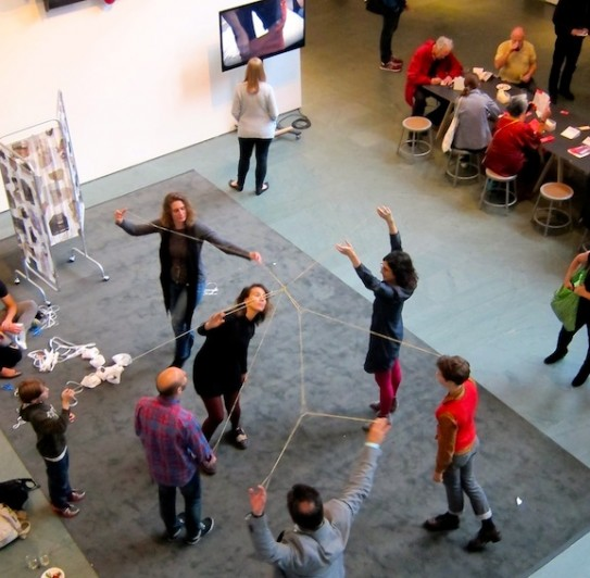 Visitors using Lygia Clark's sensorial object called Living Structures, made up of elastic bands connecting participants in a giant flexible web. Photo by Sarah Kennedy