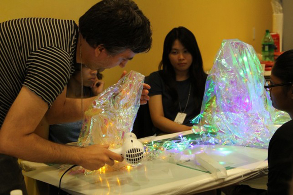 Babycastles member Robin Enrico assists teens with the production of the flashing crystals