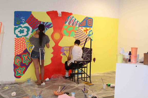 Teens working on the main mural prior to putting up the rock walls