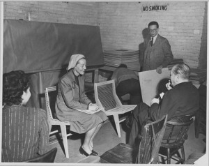 """Judging of the Competition Entries: Two Jurors, Catherine Bauer and Ludwig Mies van der Rohe, discussing an entry.Edgar Kaufmann, Jr., Competition Director standing in background."" Publicity photograph released in connection with the exhibition, ""Prize Design for Modern Furniture."" 1950"