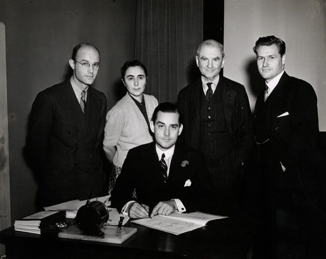 July 1935 signing of the document establishing the MoMA Film Library. From left: John Abbott, Iris Barry, John Hay Whitney (seated), A. Conger Goodyear, Nelson A. Rockefeller