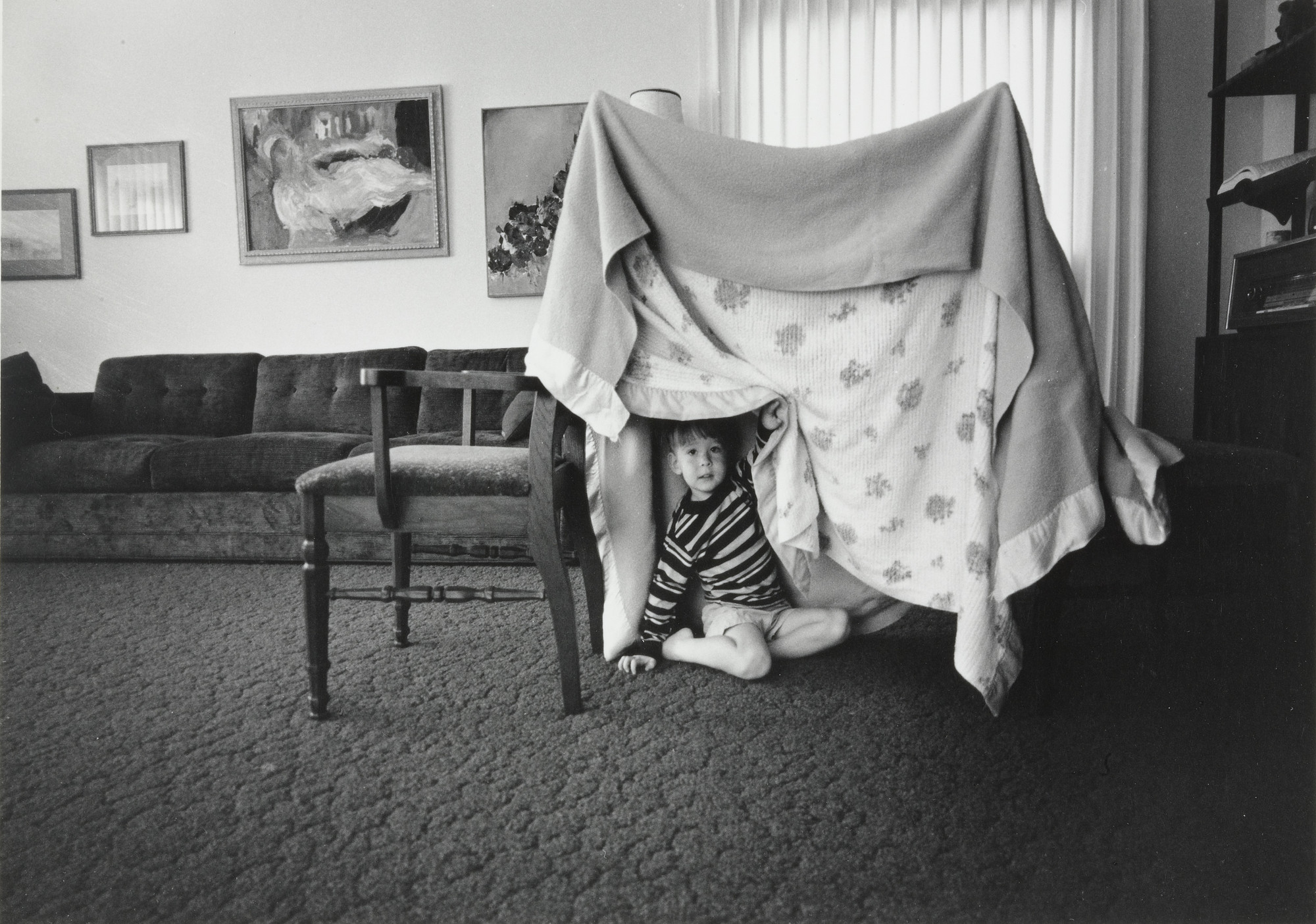 Bill Owens. Some days when there is no one to play with I build Glenn a tent play house out of two chairs and two blankets.. 1971