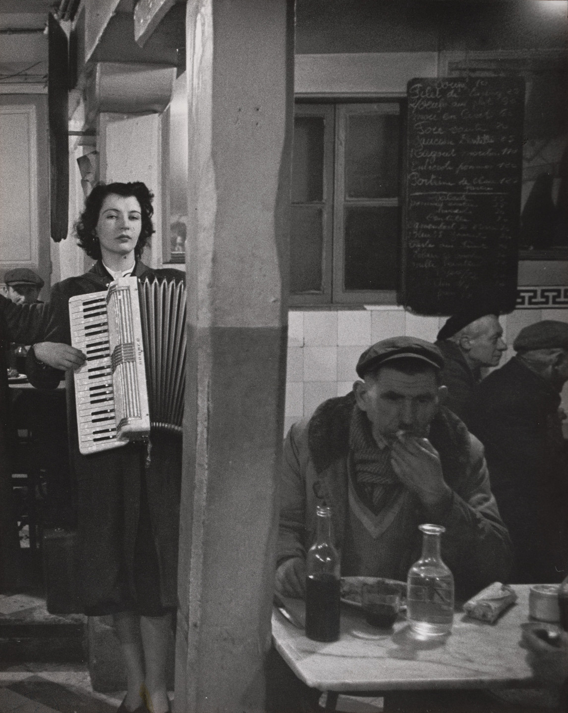 Robert Doisneau. Accordionist Playing in a Bistro near Les Halles, Paris. c. 1950