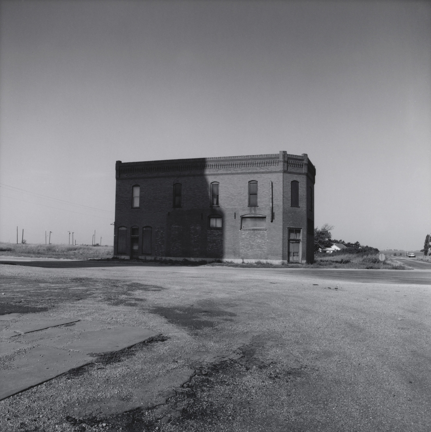 Frank Gohlke. Brick Building in the Shadow of a Grain Elevator - Cashion, Oklahoma. 1973-74