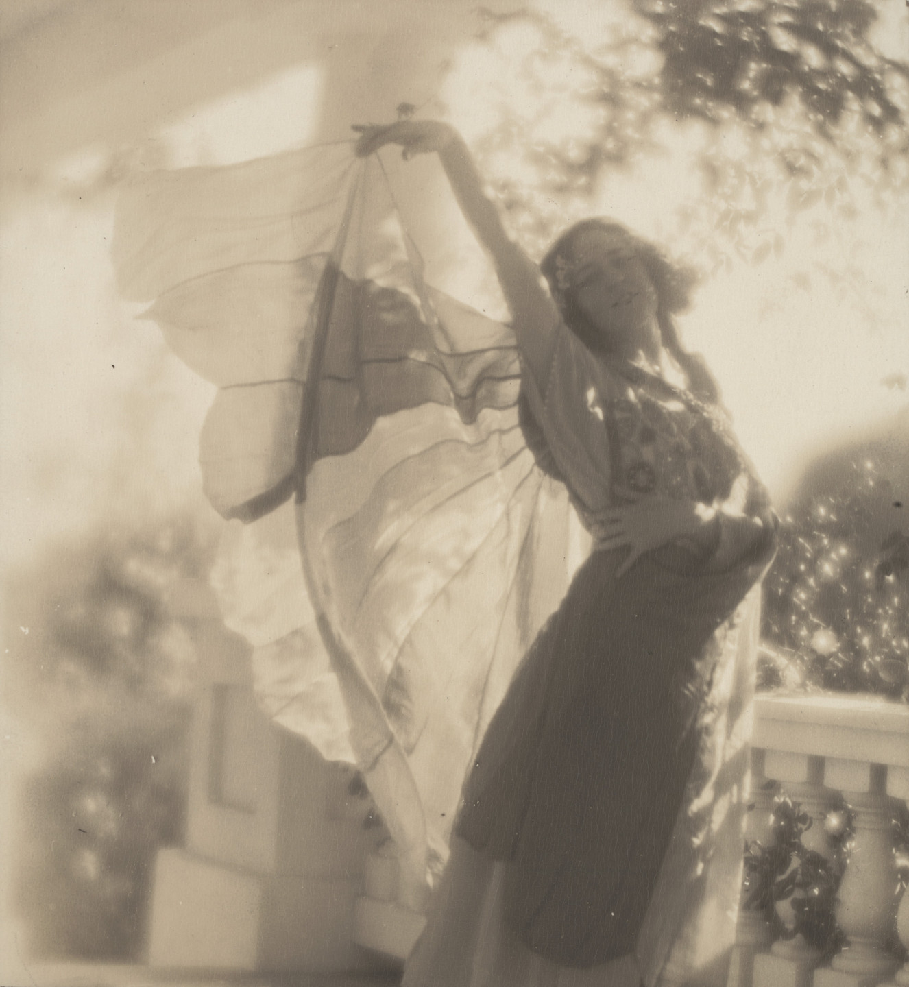 Edward Weston. Violet Romer. (standing on porch, lifting veil). c. 1917