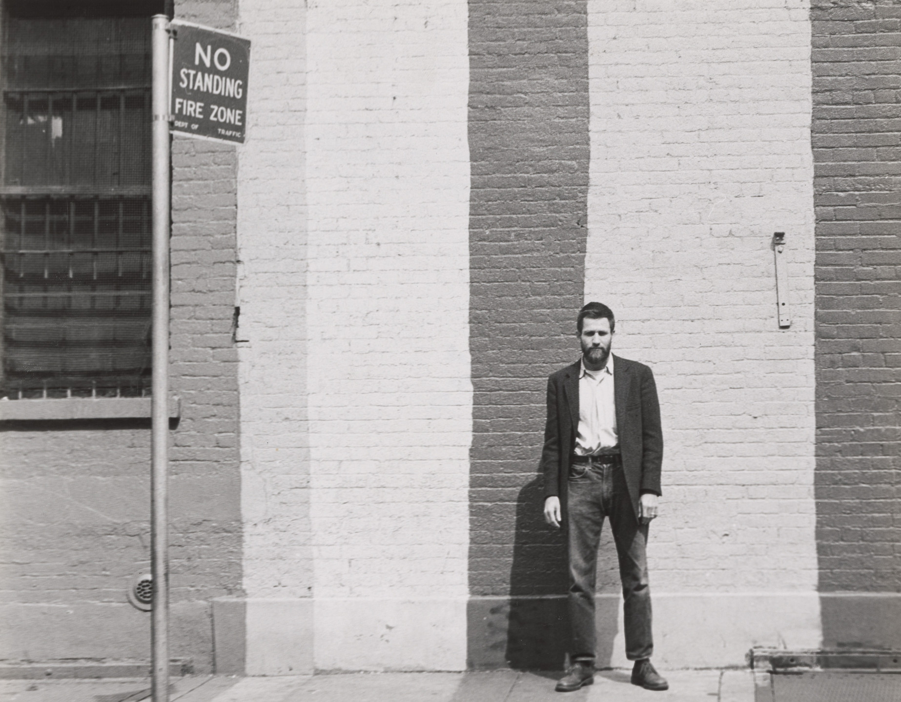 Fred W. McDarrah. Allan Kaprow portrait in front of painted brick wall. 1959