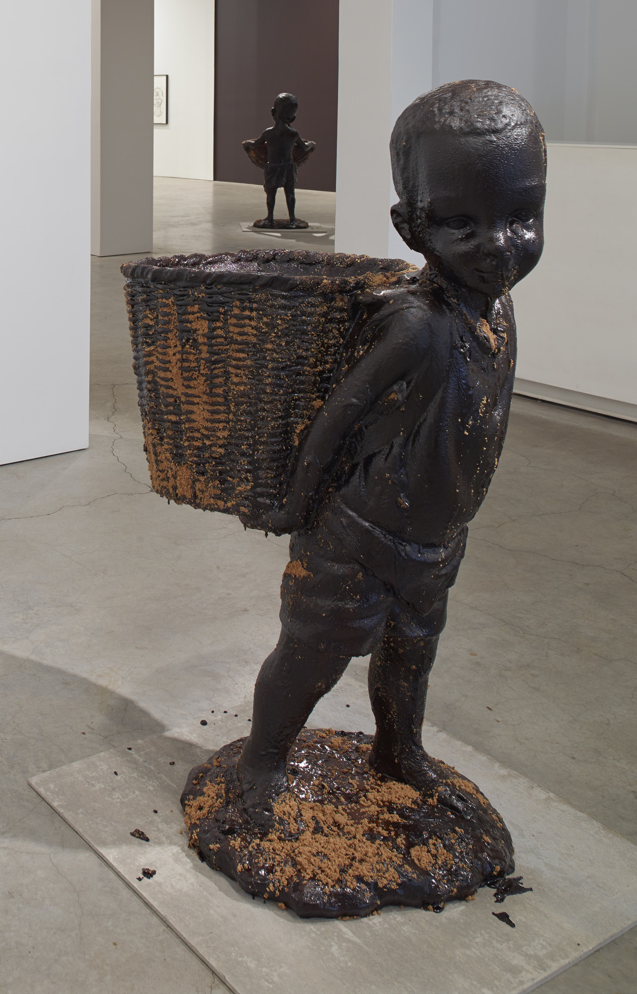"Kara Walker. African Boy Attendant Curio with Molasses and Brown Sugar, from ""The Marvelous Sugar Baby"" Installation at the old Domino Sugar Factory Warehouse. (Rear Basket),. 2014"