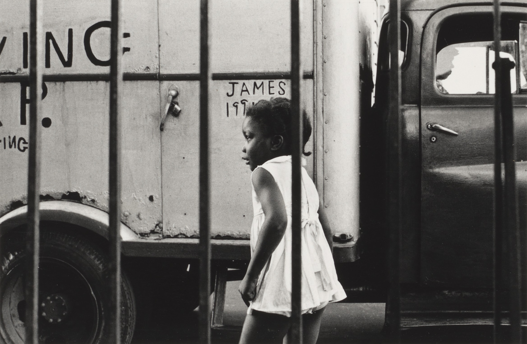 Shawn W. Walker. Young Girl in Front of Truck, 120th Street, Harlem, NY. 1962