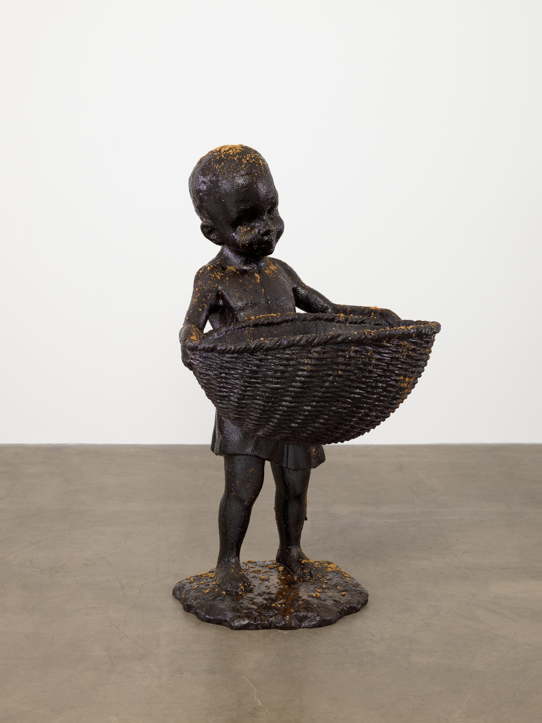 "Kara Walker. African Boy Attendant Curio with Molasses and Brown Sugar, from ""The Marvelous Sugar Baby"" Installation at the old Domino Sugar Factory Warehouse (Front Basket). 2014"