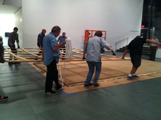 Installation team lays the stretcher across the back of the canvas