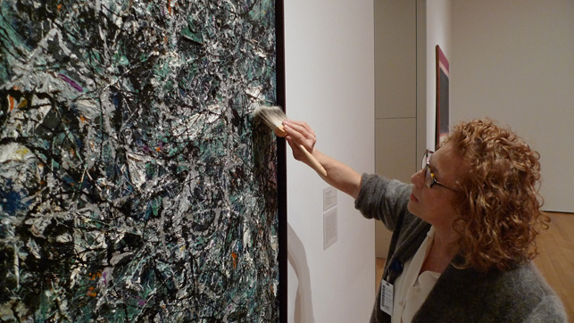 Conservators routinely inspect and dust the works on view in the galleries. Here, paintings conservator Anny Aviram dusts Jackson Pollock's Full Fathom Five (1947)