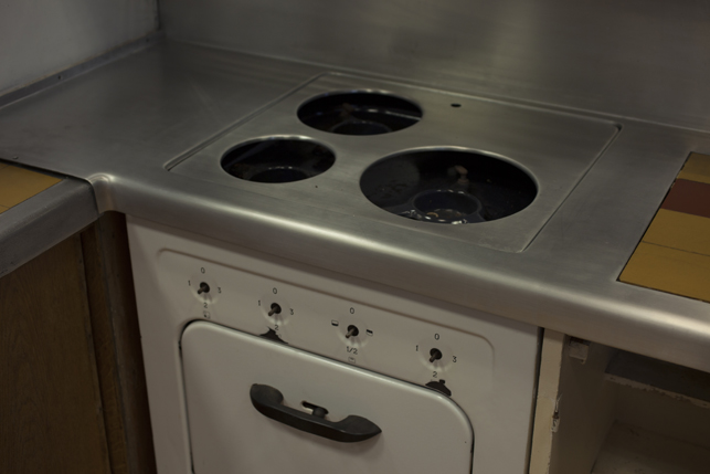 Detail of the kitchen stove, which is missing both the dials for the grills as well as the electric grills themselves.