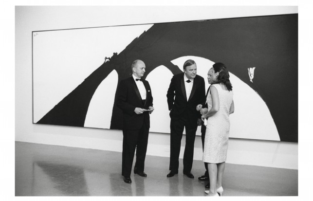 Center, Robert Motherwell at the opening of the exhibition, Robert Motherwell,  September 28, 1965. The Museum of Modern Art, New York. Gelatin-silver print, 8 x 10″ (20.3 x 25.4 cm). Museum-Related Photographs, 30. The Museum of Modern Art Archives, New York. Photo by Allyn Baum