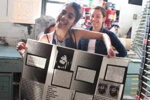 Alya and Stephanie posing with an unfolded zine.