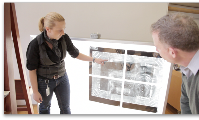 Conservators Cindy Albertson and Michael Duffy examine an x-ray of René Magritte's The Portrait