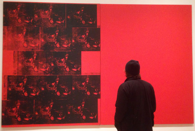 "Joe Bradley examines Orange Car Crash Fourteen Times. 1963. Silkscreen ink on synthetic polymer paint on two canvases, 8' 9 7/8"" x 13' 8 1/8"" (268.9 x 416.9 cm). The Museum of Modern Art, New York. Gift of Philip Johnson. © 2015 Andy Warhol Foundation for the Visual Arts/Artists Rights Society (ARS), New York. Photograph by Naomi Kuromiya"