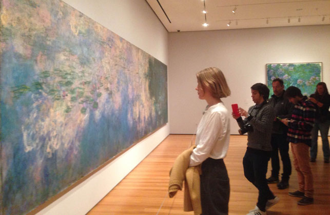 """Dianna Molzan in the galleries with Water Lilies. Shown: Claude Monet (French, 1840–1926). Water Lilies. 1914–26. Oil on canvas, three panels, each 6' 6 3/4"""" x 13' 11 1/4"""" (200 x 424.8 cm), overall 6' 6 3/4"""" x 41' 10 3/8"""" (200 x 1276 cm). Mrs. Simon Guggenheim Fund"""