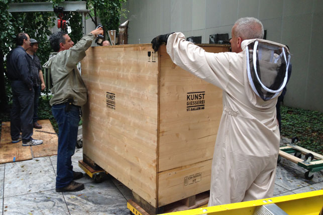Beekeeper Andrew Cote (left) and a member of the installation team open the crate. Photo: Margaret Ewing