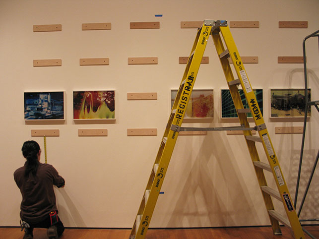 Installing Basim Magdy's The Hollow Desire to Populate Imaginary Cities. 2014. Thirty chromogenic color prints from chemically altered slides on metallic paper. Commissioned by Art in General, New York, in collaboration with HOME, Manchester, U.K. Courtesy the artist and Marisa Newman Projects. Photo: Kristen Gaylord