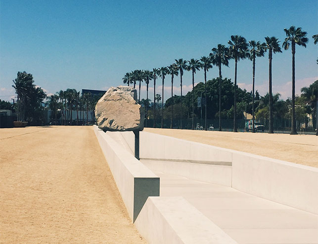 A view of the LACMA exterior. Shown: Michael Heizer. Levitated Mass. 2012. Diorite granite and concrete, 35 × 456 × 21 2/3' (10.67 × 138.98 × 6.6 m). Purchased with funds provided by Jane and Terry Semel, Bobby Kotick, Carole Bayer Sager and Bob Daly, Beth and Joshua Friedman, Steve Tisch Family Foundation, Elaine Wynn, Linda, Bobby, and Brian Daly, Richard Merkin, MD, and the Mohn Family Foundation, and dedicated by LACMA to the memory of Nancy Daly. Transportation made possible by Hanjin Shipping Holdings Co., Ltd. (M.2011.35). Photo: Annikka Olsen